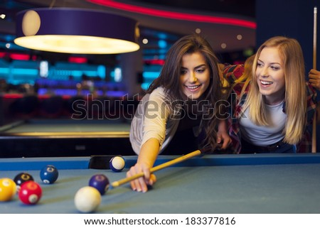Two female friends enjoying pool game - stock photo