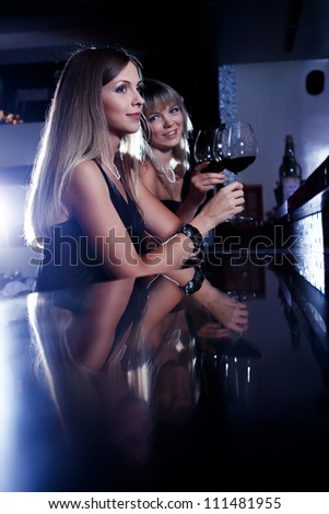 Two female friends enjoying wine at the restaurant bar