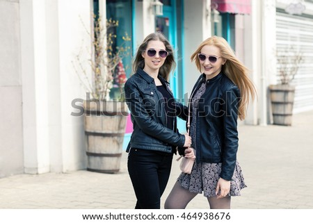 Two female friends having fun outside. Fashion and shopping. Happines and friendship