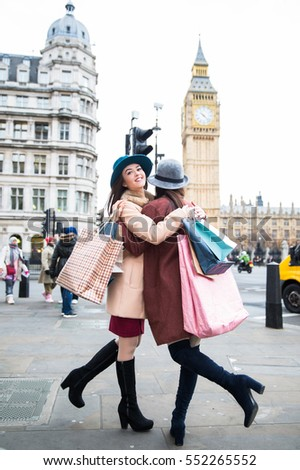 Two female friends hugging with shopping bags at London. View Big ben