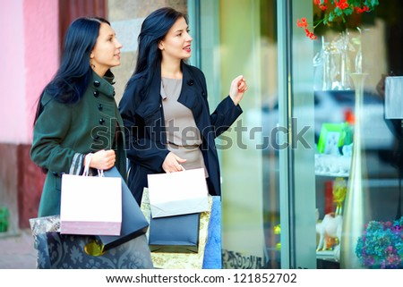 two female friends looking into the shop window
