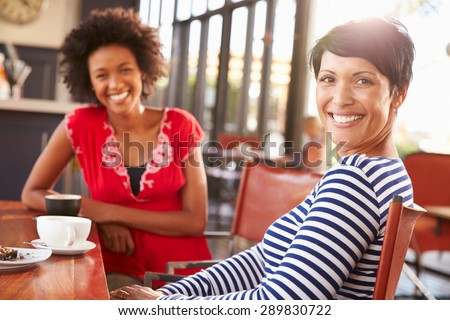 Two female friends meeting at a coffee shop - stock photo