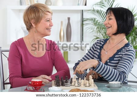 Two female friends playing chess together - stock photo