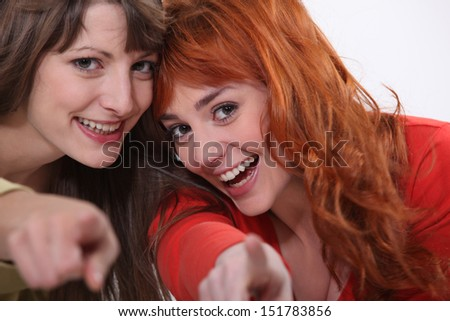 Two female friends pointing at the camera. - stock photo