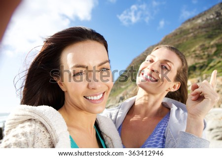 Two female friends smiling and taking selfie outdoors - stock photo