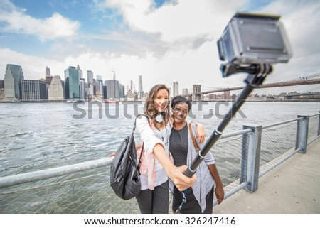 Two female friends taking a picture of New York and Brooklyn Bridge - Best friends traveling and recording their trip with a action camera - stock photo
