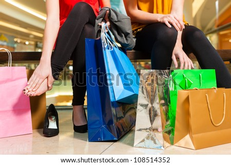 Two female friends with shopping bags having fun while shopping in a mall, the feet hurt already - stock photo