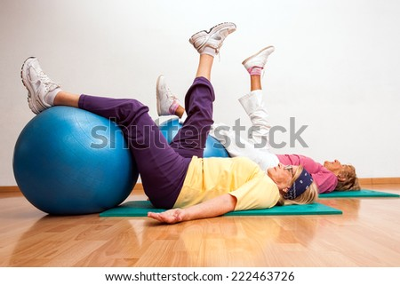Two female golden agers working out with fitness balls in health club. - stock photo