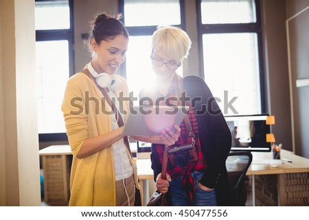 Two female graphics designer using digital tablet in office - stock photo
