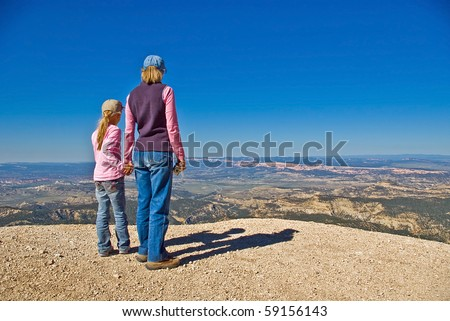 Two female hikers stand atop a peak with views of Bryce Canyon National Park and southern Utah. - stock photo