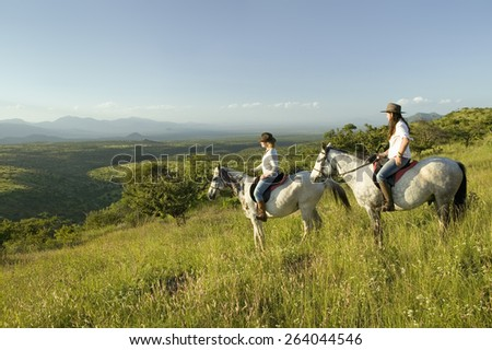 Two female horseback riders on horseback ride at sunset as one points overlooking the valley of Lewa Wildlife Conservancy in North Kenya, Africa - stock photo