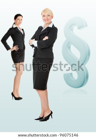 Two female lawyers standing next to big paragraph sign - stock photo