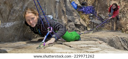 Two female rock climbers. Blond climber is leading, brunette climber is belaying. Narrow horizontal composition fits most of website headers