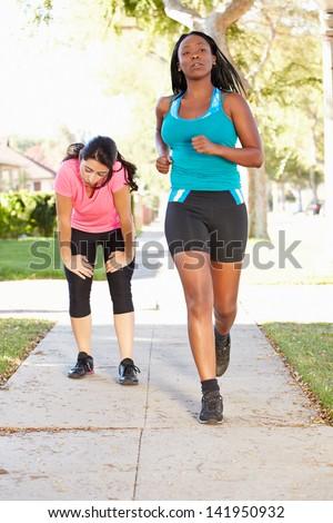 Two Female Runners Exercising On Suburban Street - stock photo
