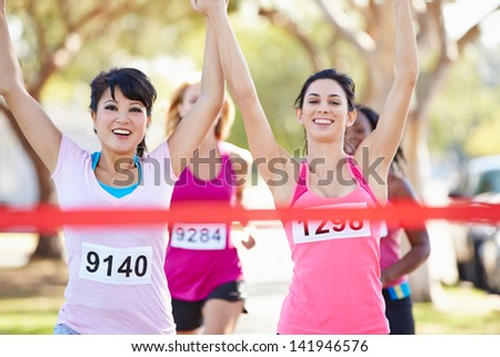Two Female Runners Finishing Race Together - stock photo