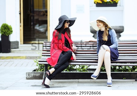 Two female sitting on a bench together - stock photo