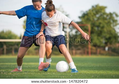 two female soccer players on the field - stock photo