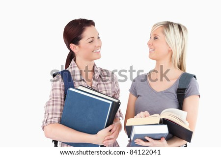 Two female students with books looking at each other