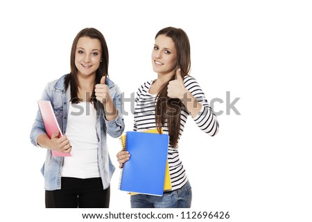 two female students with exercising books showing thumbs up on white background