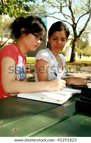 Two female students working together - stock photo