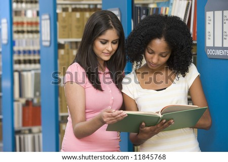 Two female students working together in library - stock photo