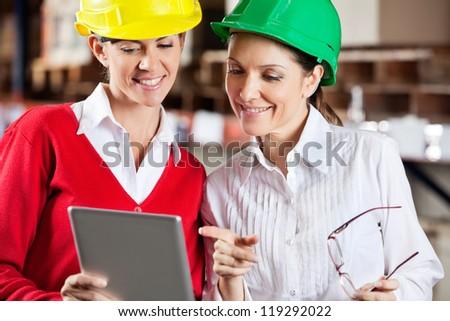 Two female supervisors using digital tablet in warehouse - stock photo