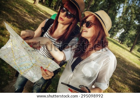 Two Female Tourists In Nature Browsing Map