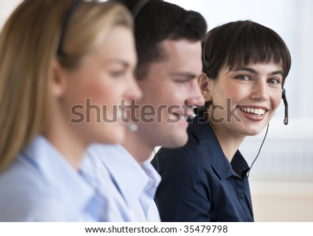 Two females and one male customer service representatives smiling.  They are working on computers and are wearing headsets.  One of the females is looking directly at the camera.