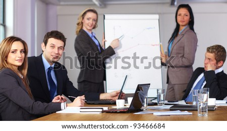 Two females standing and present graph on flipchart during business meeting, while three people sitting at conference table, focused on female on left - stock photo