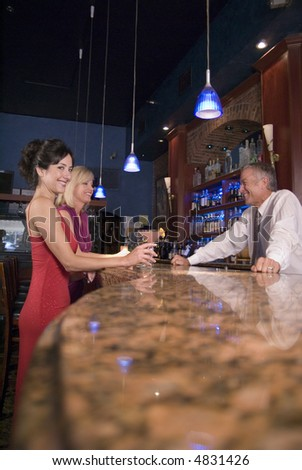 two females talk to a bartender - stock photo