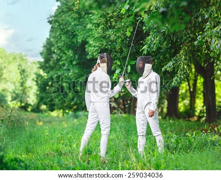 Two fencers women staying in park with crossed rapiers getting ready for competition - stock photo