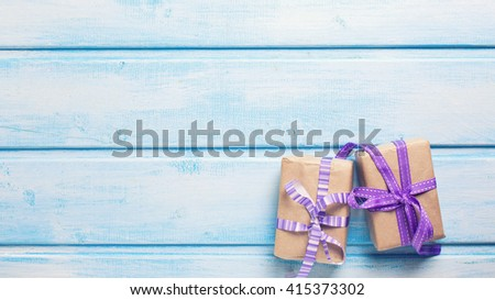 Two festive gift boxes with presents on blue wooden background. Selective focus. Place for text. Toned image. - stock photo