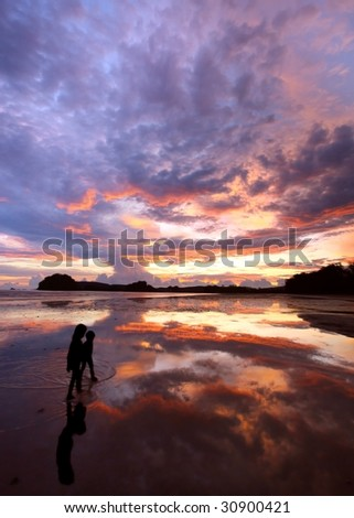 two figures on a beach at sunset - stock photo