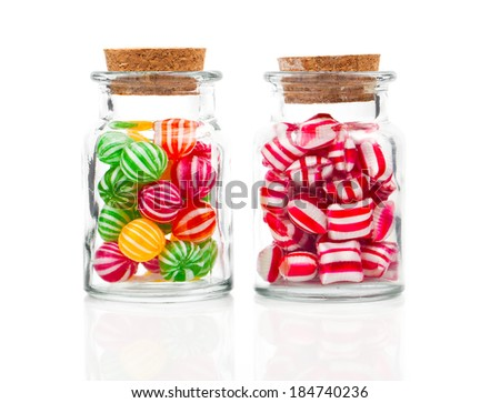 two filled glass candy jars isolated over white background - stock photo