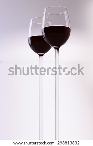 Two filled with long stems glass goblets with dessert red grapes wine standing close to each other isolated on grey and white backgroung, vertical picture - stock photo