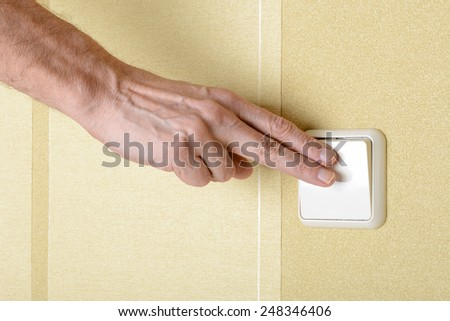 Two fingers switching, in or off, the light with a big square security electric interrupter - stock photo