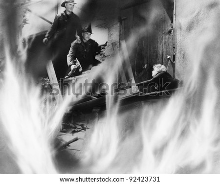 Two fire fighters rescuing a woman - stock photo