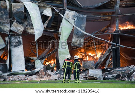 Two firefighters looking at a building that is detroyed by a huge fire - stock photo