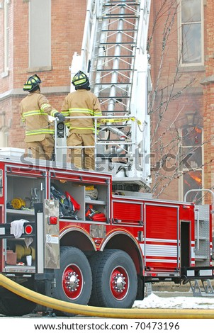 Two firefighters standing on firetruck with ladder extended to a burning building. - stock photo