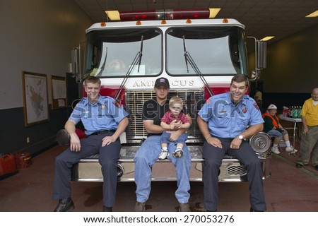 Two firemen, father and son sit on fire truck in Americus Georgia - stock photo