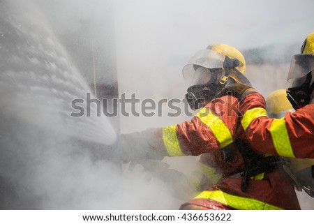 two firemen in oxygen mask helmet and fire fighting suit spraying water to fire surround with smoke and drizzle - stock photo