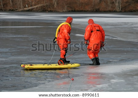 two firemen walking on ice preparing to practice saving technique - stock photo