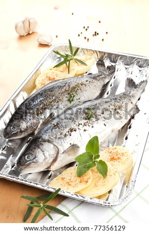Two fish on grilling plate with potatoes and herbs prepared for grilling. Garlic and herbs in background. - stock photo