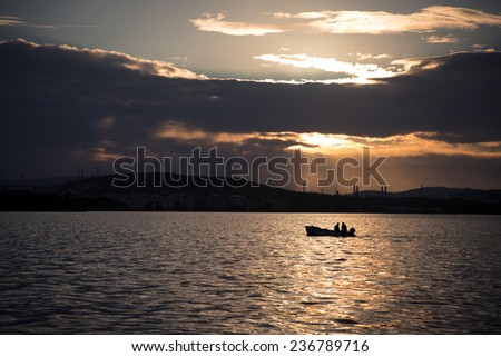 Two fisher men on a boat in the sea in the evening. - stock photo