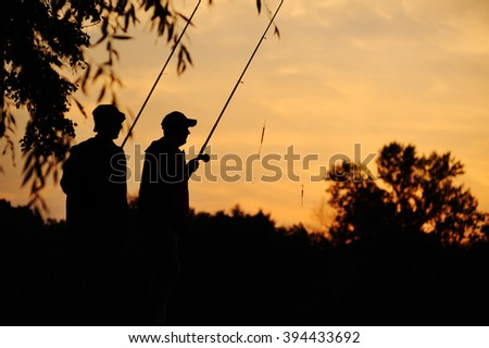 two fisherman at sunset. silhouettes of fishermen - stock photo