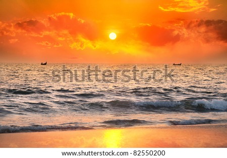 Two Fisherman boats catching fish in the ocean at sunset dramatic sky background in Kerala, India - stock photo