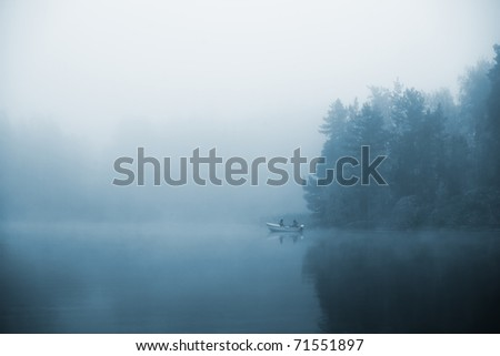 Two fishermans in the boat - stock photo