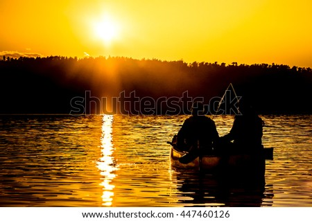 Two fishermen are silhouetted against an orange sunset on a lake in the Boundary Waters Canoe Area in the North Woods of northern Minnesota.This is the American side of Quetico National Park in Canada - stock photo