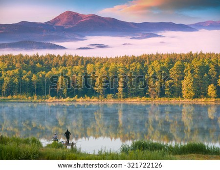 Two fishermen fishing from the key in high mountain blue lake. Beautiful yellow autumn forest reflected in water. - stock photo