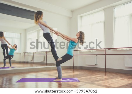 Two fit pretty women are doing balance exercise - stock photo